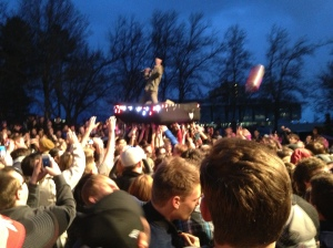MUTEMATH lead singer, Paul Meany, surf the crowd on an inflated mattress festooned with Christmas lights.